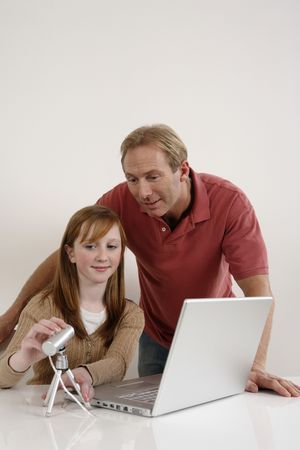 Girl adjusting web camera while a man looks on photo