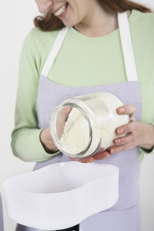 Woman pouring flour onto weight scale