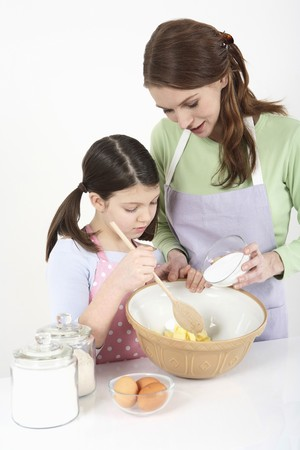 Woman mixing sugar with butter, girl watching photo