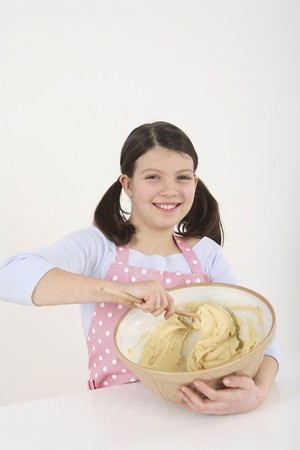Girl mixing batter in the mixing bowl