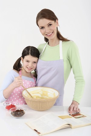 english ethnicity: Woman and girl posing for the camera while baking in the kitchen Stock Photo