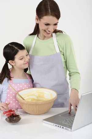 Woman and girl reading recipe from the laptop while baking in the kitchen photo
