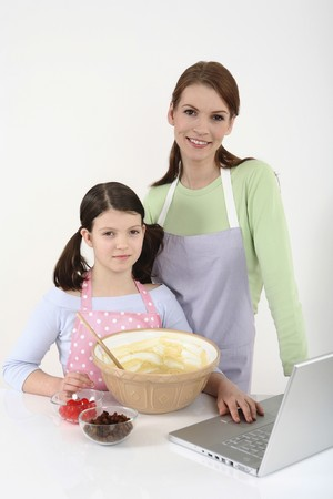 Woman and girl posing for the camera while baking in the kitchen photo