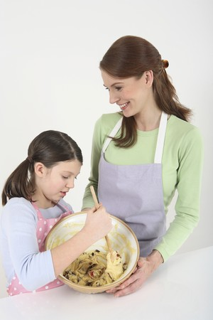 english ethnicity: Girl mixing batter in mixing bowl, woman helping to hold the bowl Stock Photo