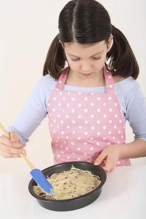 Girl spreading batter on baking pan