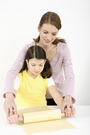 Woman and girl kneading dough with rolling pin