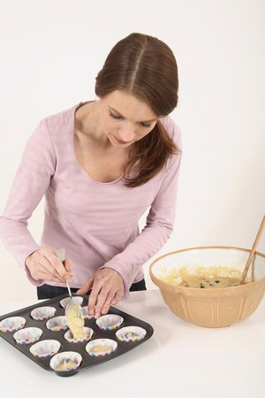 Woman spooning pastry mixture into muffin liners on baking tray