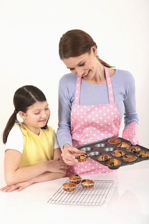 Woman transferring muffins from the baking tray to the wirerack photo