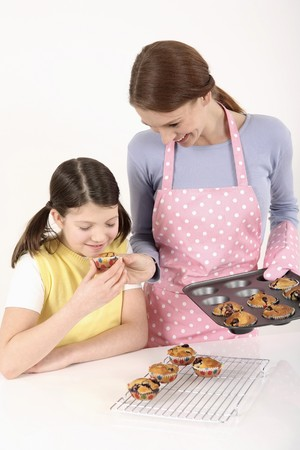 Girl enjoying the aroma of the freshly baked muffin, woman smiling while watching