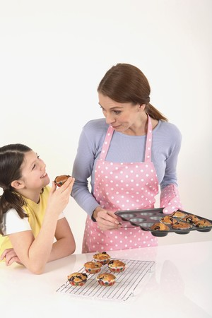 Girl getting a freshly baked muffin from woman photo