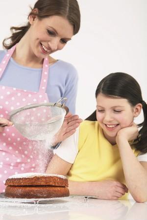 Mujer de tamizado de harina de pastel, niña sonriente mientras ve