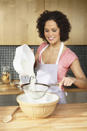 english ethnicity: Woman pouring flour into sieve