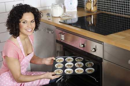 domestic kitchen: Woman placing tray into oven