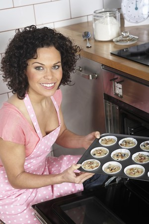english ethnicity: Woman placing tray into oven