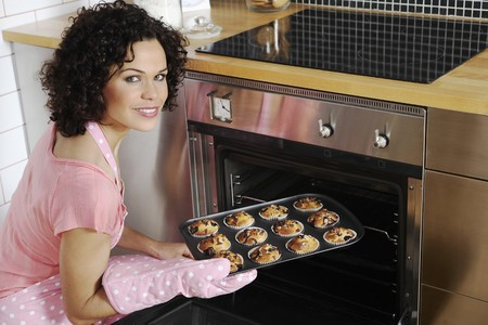 english ethnicity: Woman taking tray out of oven