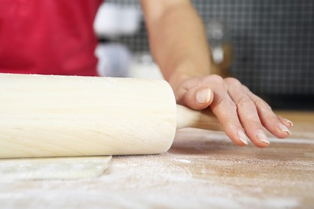 Woman kneading dough with rolling pin Banco de Imagens