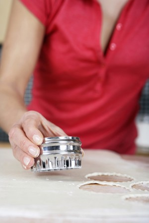 Woman cutting dough with pastry cutter photo