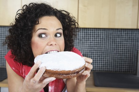 english ethnicity: Woman looking away while biting on cake