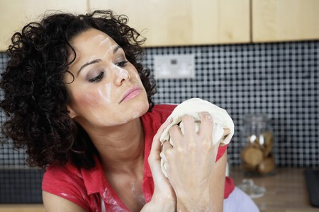 Woman with flour on her face looking at dough Banco de Imagens