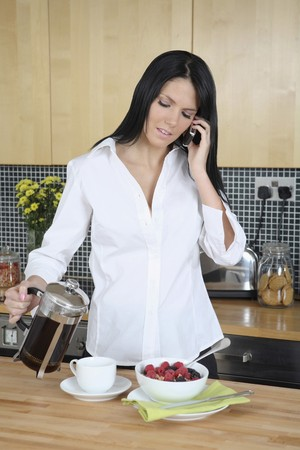 Businesswoman pouring coffee while talking on the phone photo