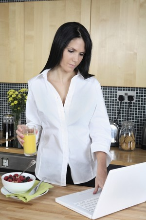 Businesswoman with a glass of orange juice using laptop photo
