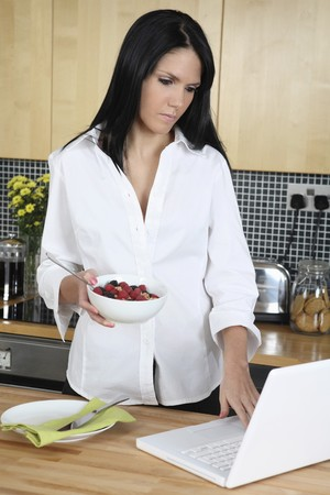 english ethnicity: Businesswoman holding a bowl of breakfast cereal while using laptop Stock Photo