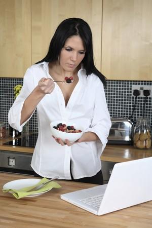 Businesswoman disfrutar de un taz�n de cereales para el desayuno, mientras que utilizando port�til Foto de archivo