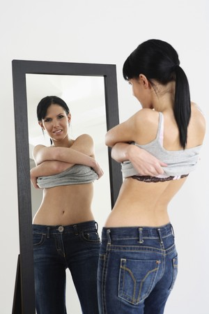 Woman removing her tank top while looking at the mirror photo