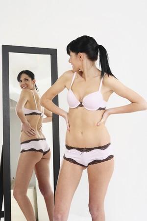 鏡の前でポーズをとってランジェリーの女性 写真素材