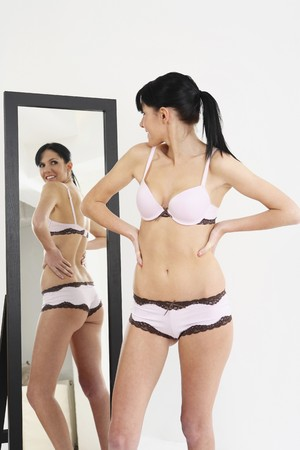 Woman in lingerie posing in front of mirror photo