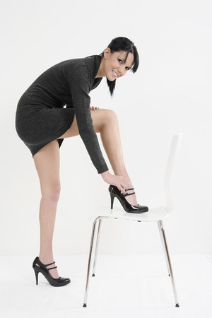 Woman adjusting strap on shoe photo