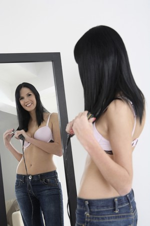 Woman straightening hair photo