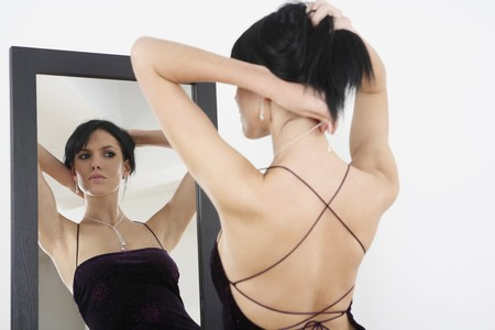 Woman in evening gown putting on necklace Stock Photo