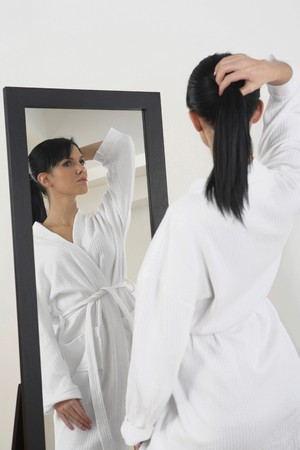 Woman in bathrobe posing in front of mirror