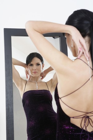 Woman in evening gown putting on necklace photo