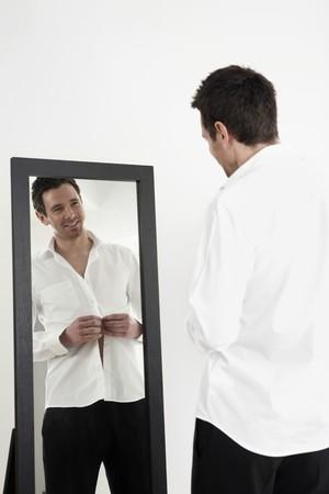 Empresario de pie delante del espejo, botonadura de su camisa Foto de archivo
