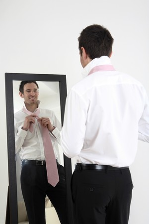 with reflection: Businessman standing in front of mirror tying necktie Stock Photo