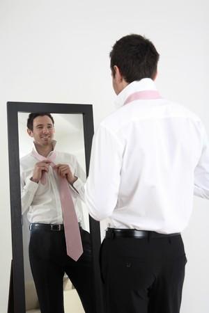 Businessman standing in front of mirror tying necktie Stock Photo