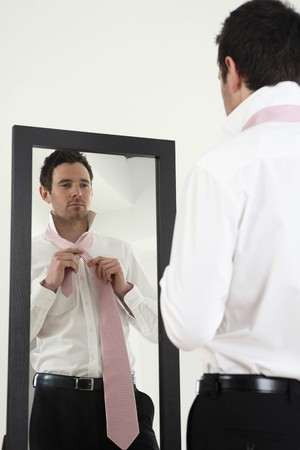 Businessman standing in front of mirror tying necktie Stock Photo