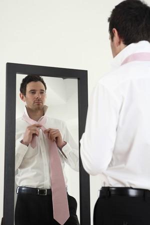 spiegels: Zakenman staande tegenover spiegel koppelende stropdas