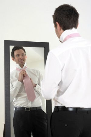 Businessman standing in front of the mirror tying necktie