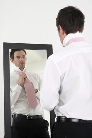 Businessman standing in front of the mirror tying necktie