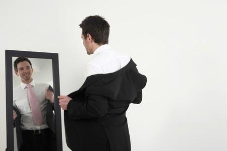 Empresario de pie frente al espejo usando su abrigo