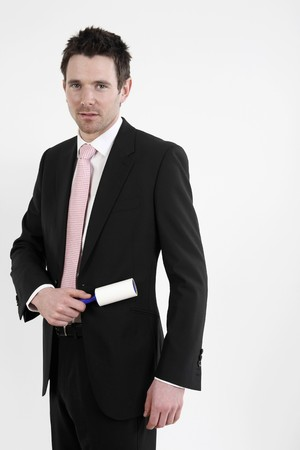 lint: Businessman using lint roller on his coat Stock Photo