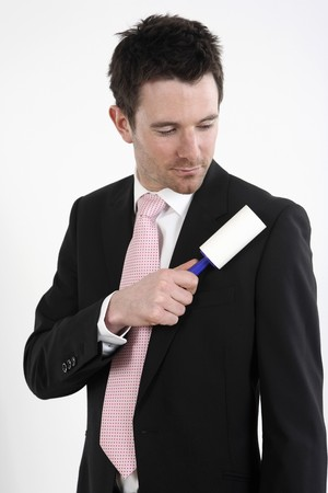 english ethnicity: Businessman using lint roller on his coat Stock Photo