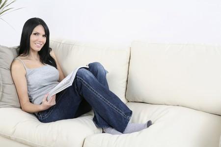 Mujer sentada en el sofá, sonriente mientras sostiene la revista Foto de archivo