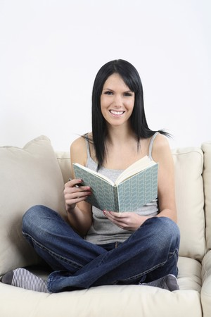 Woman sitting on the couch, smiling while holding pen and diary photo