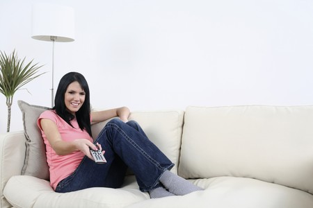 english ethnicity: Woman sitting on the couch, using remote control