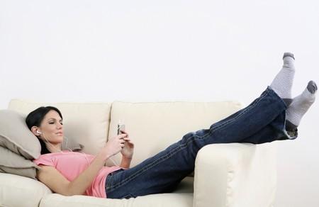 Mujer tumbada en el sofá, escuchar MP3 Foto de archivo