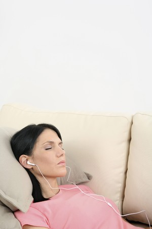 Woman lying down on the couch, listening to MP3 player with her eyes closed Stock Photo - 4099510